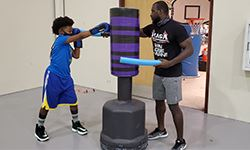 A young boy boxing a punching bag with his coach