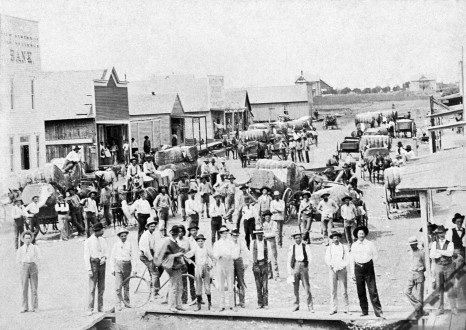 Black and White Photo of Men Standing in Old Downtown Garland